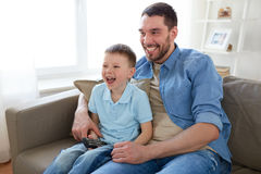 Father and son with remote watching tv at home Stock Images