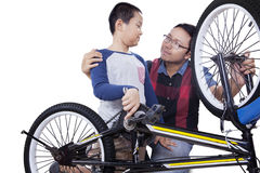 Father and son repair the bike together Stock Photo