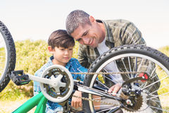 Father and son repairing bike Stock Photos