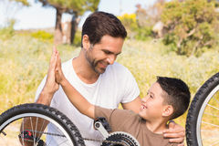 Father and son repairing bike together Stock Photography