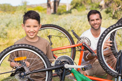 Father and son repairing bike together Stock Images