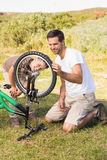 Father and son repairing bike together Stock Photos
