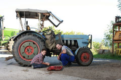 Father and son repairing a tractor Royalty Free Stock Image