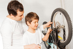 Father with son replacing cable in bicycle brakes Stock Photography