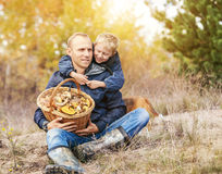 Father with son rest in autumn forest Stock Photos