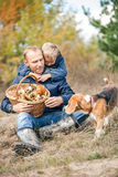Father and son rest on forest glade after mushrooms pick Royalty Free Stock Photography