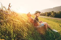 Father and son rest in high green grass after bicycle walk Royalty Free Stock Photos
