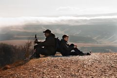 Father and son relaxing together on top of the mountain. Father and son rest in the hike to the top of the mountain Royalty Free Stock Photo