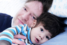 Father and son resting in bed Stock Image