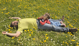 Father and son resting on a meadow. Fool of flowers royalty free stock photography