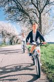 Father with son ride a bicycles on country road under the blosso. M trees at spring time Royalty Free Stock Photo