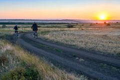 Father and son ride a bike in the country on the field in the evening Stock Photo