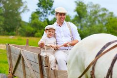 Father and son ride a horse cart Stock Photos