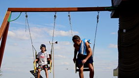 Father and son ride on the swing, swing with an iron chain. Swing the sky background, swings near the river, father and son ride on the swing, swing with an iron stock video footage