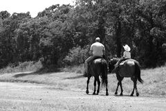 Father & Son Riding. A photograph capturing a sharing moment between father and son riding horses along the lake trails in Oklahoma Stock Photos