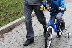 Father and son riding a Bicycle. Children`s sports entertainment. A man walks next to a Bicycle, which goes to the child. Father teaches son to ride bike Stock Images