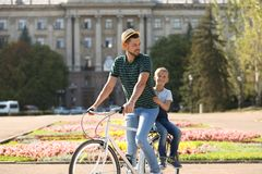 Father and son riding bicycle. On street stock photography