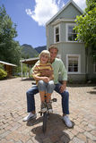 Father and son riding bicycle in patio stock photos