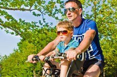 Father and son riding a bicycle. Portrait of a father and son riding a bicycle Royalty Free Stock Images