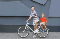 Father and son riding bicycle. On street stock photos