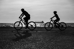 Father and son riding the bicycles together royalty free stock image