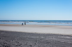 Father and son riding bikes along the shoreline on a beach in Florida Stock Photography