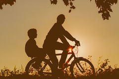 Father with son riding bikes at sunset Royalty Free Stock Photography