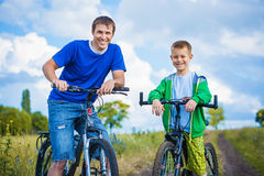 Father and son are riding in the field Stock Image