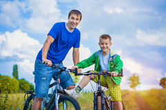 Father and son are riding in the field Royalty Free Stock Photo
