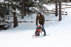 Father and son riding a sledge Royalty Free Stock Photography