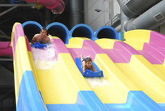 Father and son riding in the water park with slides. Father with his son in the water park with slides go Stock Photos
