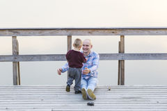Father with the son are on the river jetty. Fog. Sunset. Royalty Free Stock Image