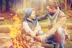 Father and son roasting marshmallow over campfire. Camping, tourism, hike and family concept - happy father and son roasting marshmallow over campfire Stock Photography