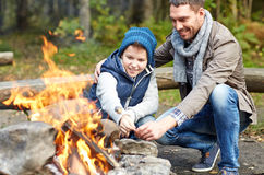Father and son roasting marshmallow over campfire Royalty Free Stock Photos