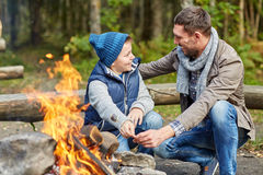 Father and son roasting marshmallow over campfire. Camping, tourism, hike, family and people concept - happy father and son roasting marshmallow over campfire Stock Photo