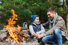 Father and son roasting marshmallow over campfire. Camping, tourism, hike, family and people concept - happy father and son roasting marshmallow over campfire Stock Images