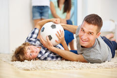 Father and son romping with ball at home Royalty Free Stock Images