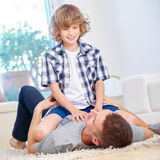 Father and son roughhousing at home. In the living room Royalty Free Stock Photos