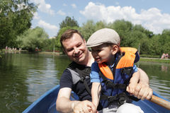 Father with son in rowboat Stock Images