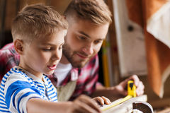 Father and son with ruler measure wood at workshop. Family, carpentry, woodwork and people concept - father and little son with ruler measuring wood plank at Stock Photography