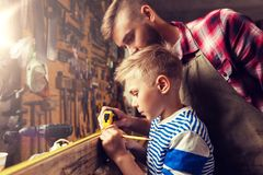 Father and son with ruler measure wood at workshop. Family, carpentry, woodwork and people concept - father and little son with ruler and pencil measuring wood Royalty Free Stock Photos