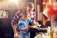 Father and son with ruler measure wood at workshop. Family, carpentry, woodwork and people concept - father and little son with ruler and pencil measuring wood Royalty Free Stock Photo