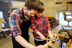 Father and son with ruler measure wood at workshop Royalty Free Stock Photo