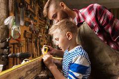 Father and son with ruler measure wood at workshop. Family, carpentry, woodwork and people concept - father and little son with ruler and pencil measuring wood Stock Photo