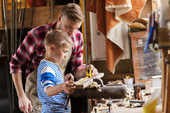 Father and son with ruler measure wood at workshop. Family, carpentry, woodwork and people concept - father and little son with ruler and pencil measuring wood Royalty Free Stock Images