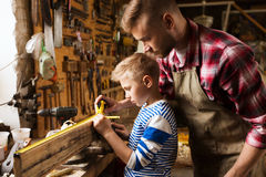 Father and son with ruler measure wood at workshop. Family, carpentry, woodwork and people concept - father and little son with ruler and pencil measuring wood Royalty Free Stock Photography