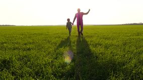 Father and son run across a green meadow, holding hands and imagining the flight of the plane. Silhouette of a happy