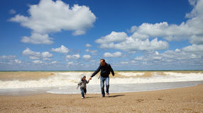 Father and son running along the beach Stock Photo