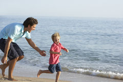 Father And Son Running Along Beach Stock Images