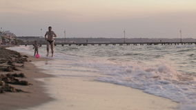 Father and son running along the beach with ball stock footage